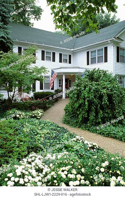 EXTERIORS: Two story Country Inn , corner covered porch entry, American flag on porch post, narrow winding gravel path , landscaped with flowers and ground...