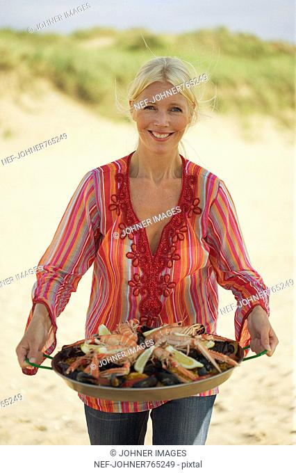 Woman on a beach with a plate of paella, Sweden