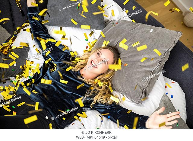Portrait of happy young woman with flying confetti at home