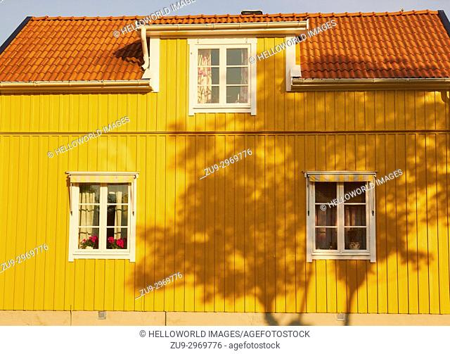 Shadow of tree on yellow painted timber house, Sweden, Scandinavia