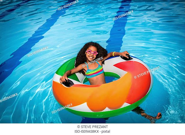 Girl sitting in inflatable ring in swimming pool looking at camera smiling