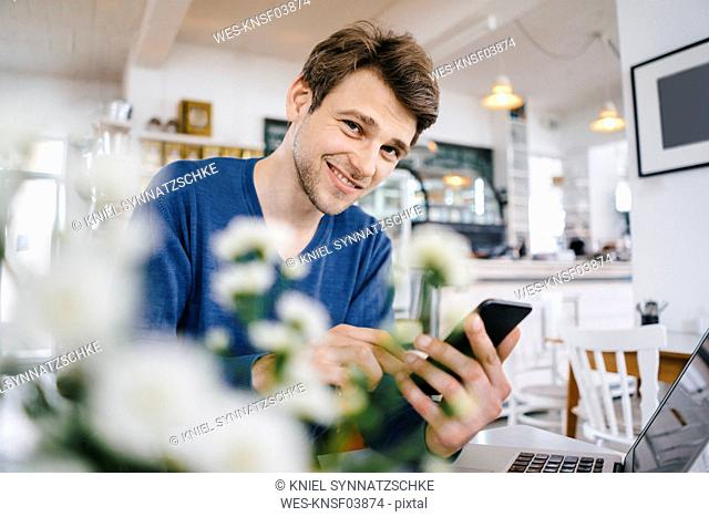 Portrait of smiling man in a cafe with cell phone and laptop