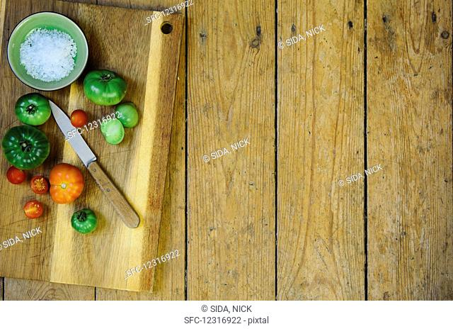 A bowl of salt and various tomatoes with a knife on a wooden chopping board