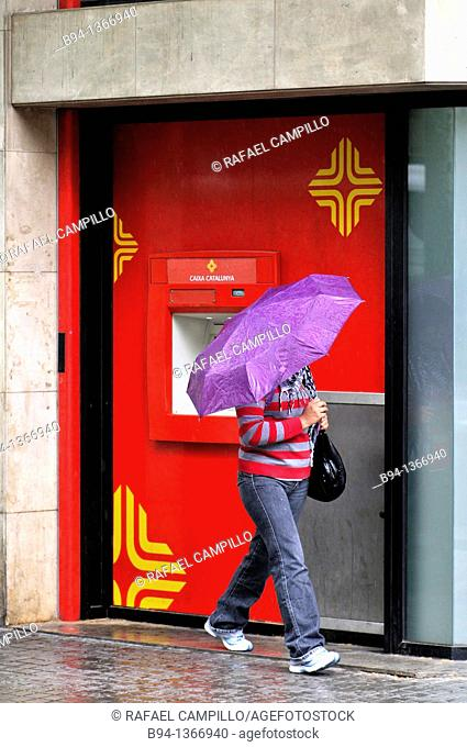 People with umbrella in front of an ATM, Barcelona. Catalonia, Spain