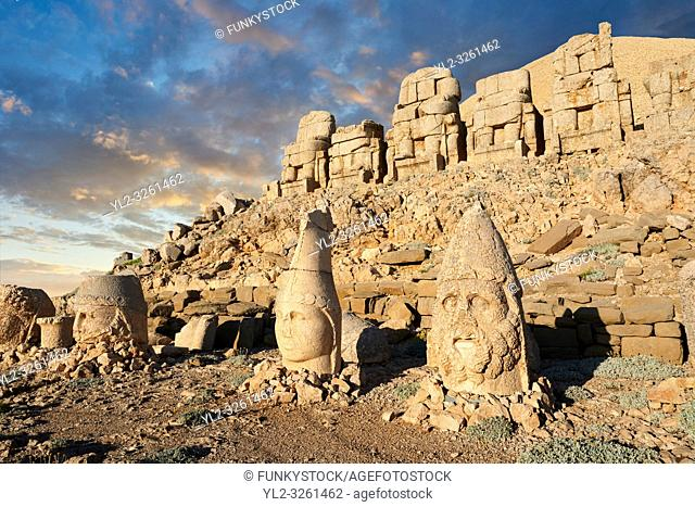 Statue heads at sunset, from right, Herekles, Apollo & Zeus, with headless seated statues in front of the stone pyramid 62 BC Royal Tomb of King Antiochus I...
