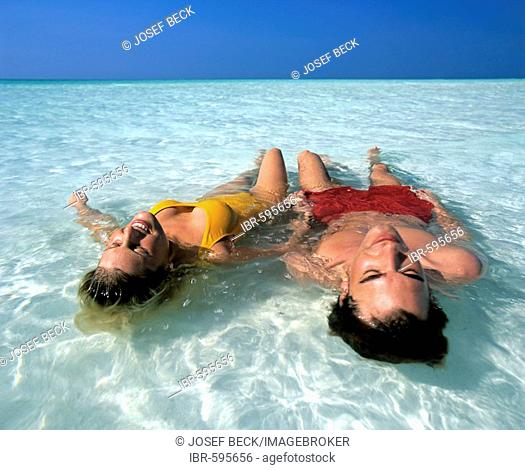 Young couple relaxing in shallow water, beach, Maldives, Indian Ocean