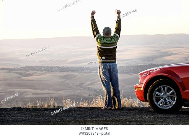 Caucasian male celebrating with his arms n the air standing next to his car at a rest stop near Lewiston, Idaho USA