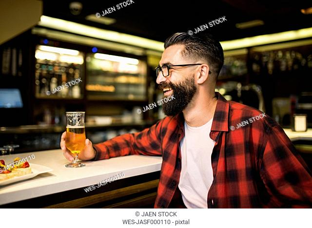 Hipster with glass of beer and tapas sitting at counter in a pub