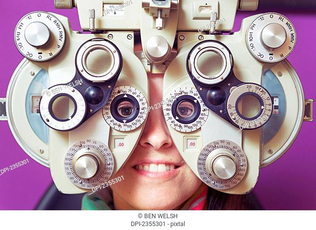 A Woman Sitting Behind Optometry Equipment In An Eye Examination; Tarifa, Cadiz, Andalusia, Spain