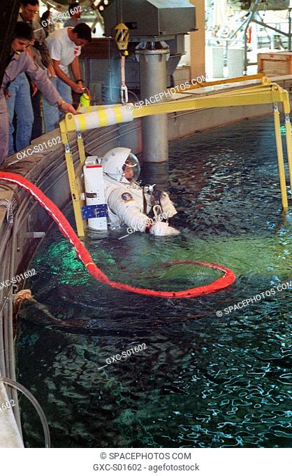 Equipped with a shuttle extravehicular mobility unit EMU space suit, astronaut Edward T. Lu watches as water rises to submerge him prior to an underwater...