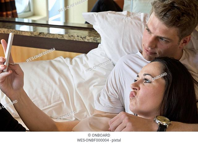 Young couple on cruise lying in bed taking selfie with smartphone