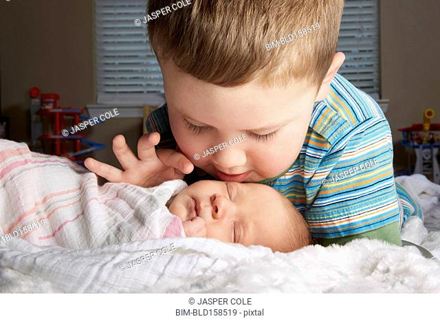 Boy admiring newborn sibling on bed