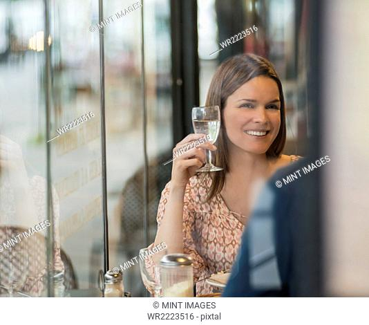 A woman sitting at a cafe table raising a glas of wine, smiling at her companion