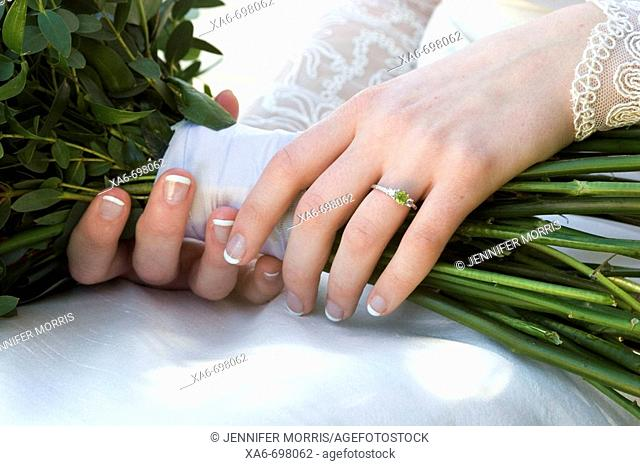A close-up of a young bride's hands as she holds her wedding bouquet. Her lace sleeves are visible and she wears a ring with a green stone