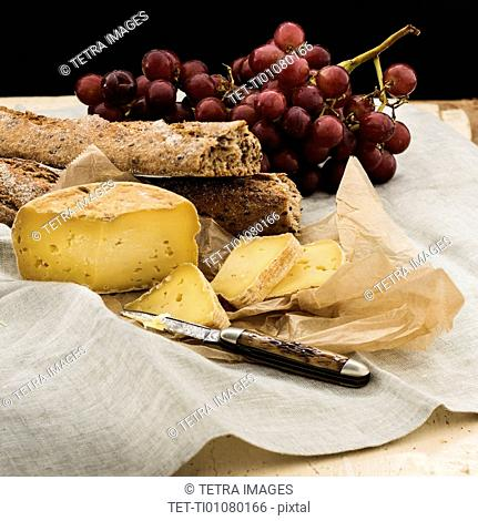 Still life with grapes and cheese and bread slices on wooden table, studio shot