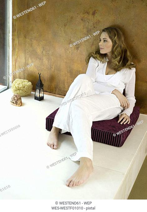 Woman sitting on cushion looking away, elevated view