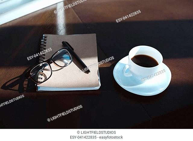 close-up view of notebook with pen, eyeglasses and cup of coffee on table top