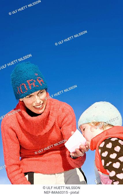 Mother and daughter having a picnic in the snow Sweden