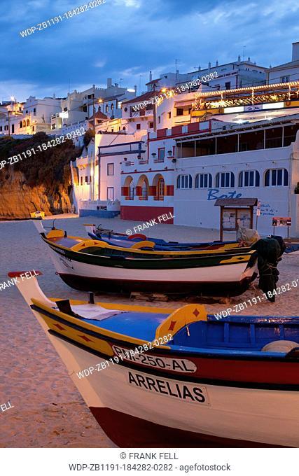 Portugal, Algarve, Carvoeiro, Colourful Fishing Boats, Beach & Town at Dusk