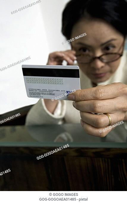 Woman examining credit card