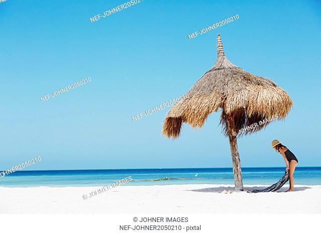 Girl standing under beach umbrella