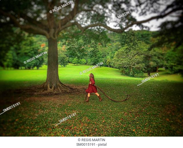 Young girl dragging a big branch while walking under a large tree in a park