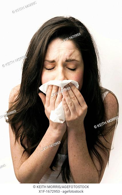 A young woman with brown hair and eyes feeling ill sneezing blowing her nose into a paper tissue
