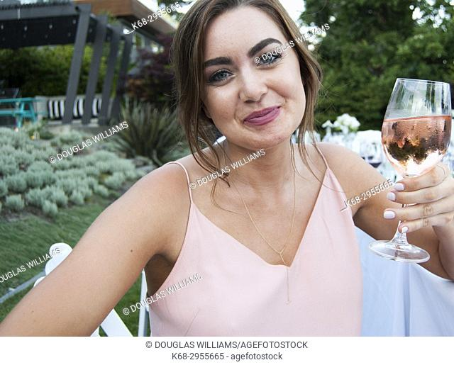 A woman, 21, holds a glass of rose wine at an outdoor wedding in West Vancouver, BC, Canada