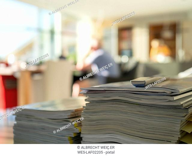 Stack of magazines in living room with man in background