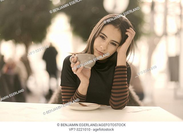 portrait of sleepy woman holding coffee cup while enjoying break at table in café, in Munich, Germany