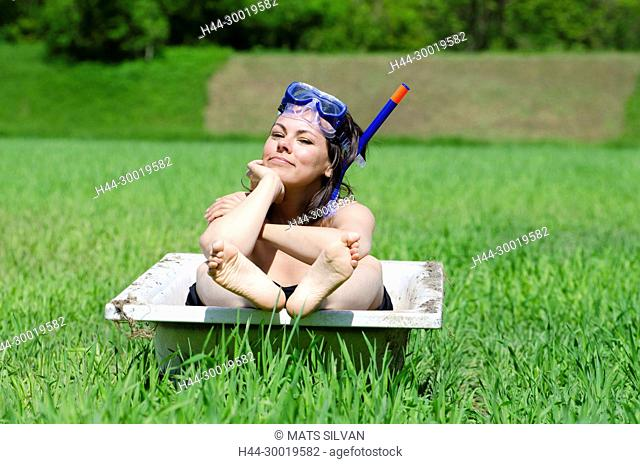 Woman Sitting in a Bathtub With Diving Mask on a Green Field in Ticino, Switzerland