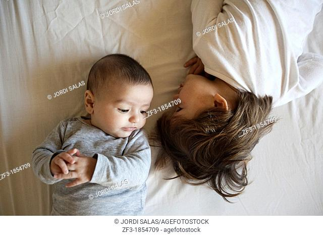 A baby and a boy playing on a bed