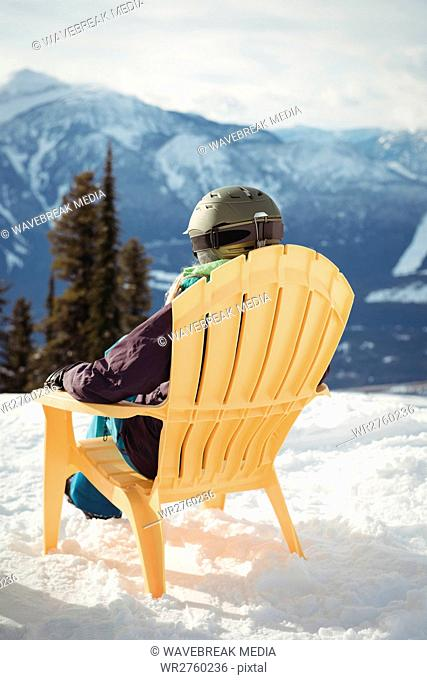 Rear view of woman sitting on chair at snow covered mountain