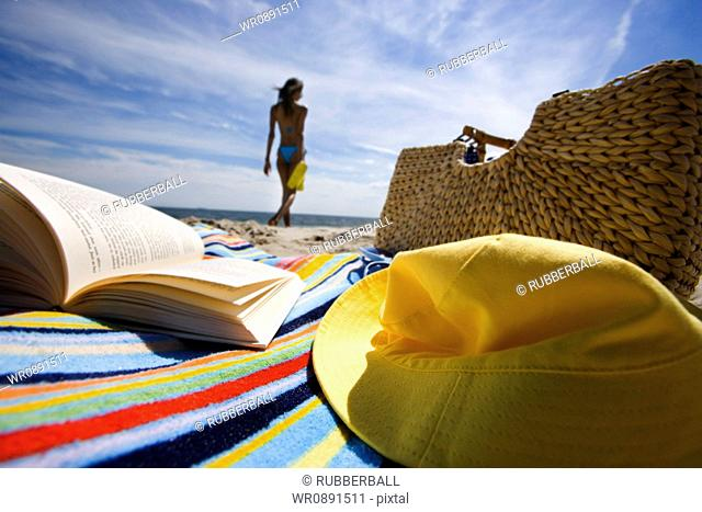 Beach towel with book and bag with a young woman in background