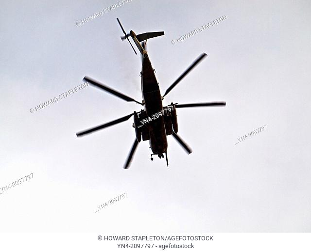A U.S. military helicopter (ch-53e) flies directly overhead