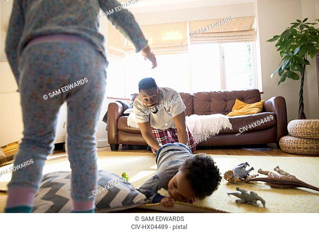 Playful father and children in living room