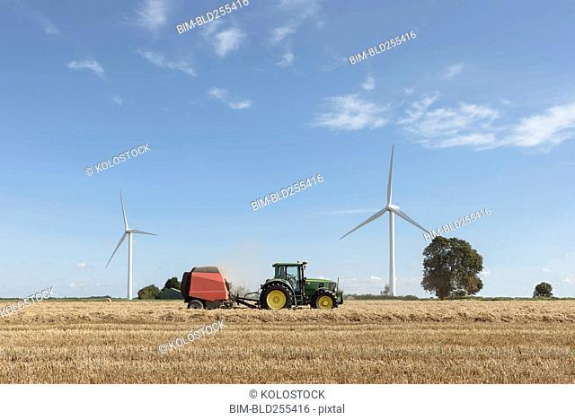 Caucasian man driving tractor near wind turbines