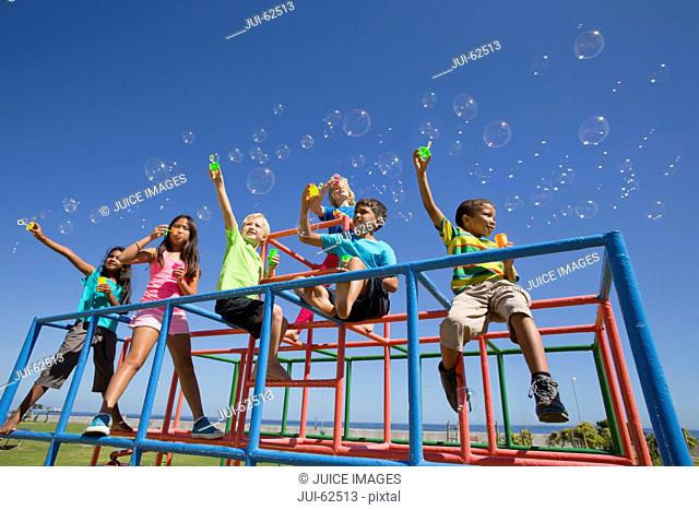 Children blowing bubbles with bubble wands on playground