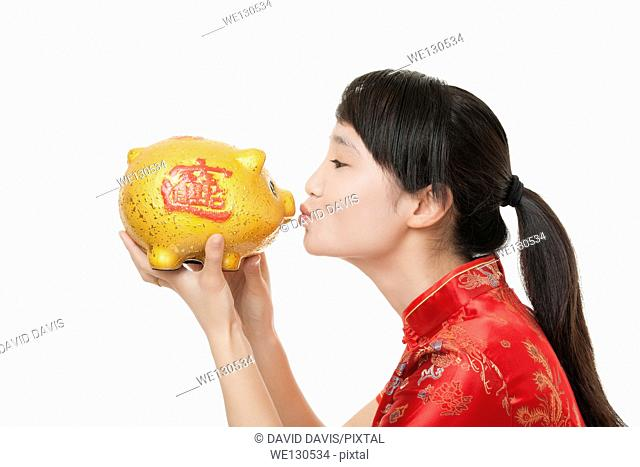 Beautiful Chinese woman wearing a traditional dress known as a Chipao holding a piggy bank