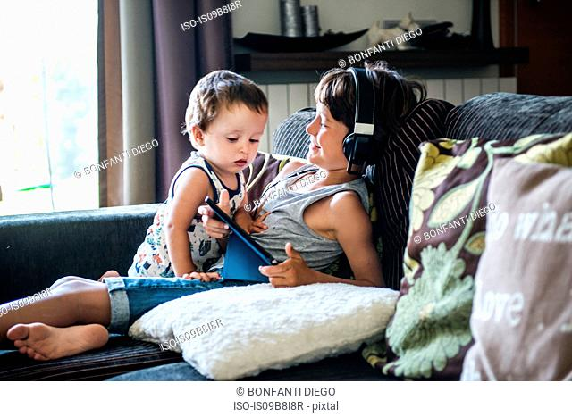 Curious male toddler looking at brother's digital tablet on sofa