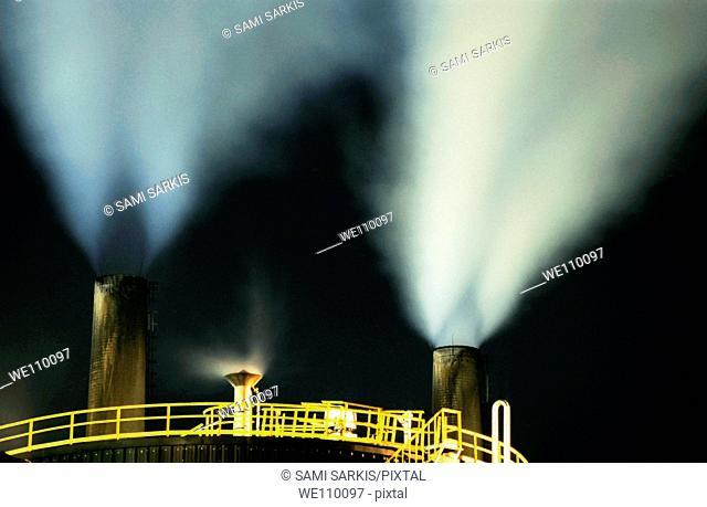 Petroleum refinery chimneys at night, France