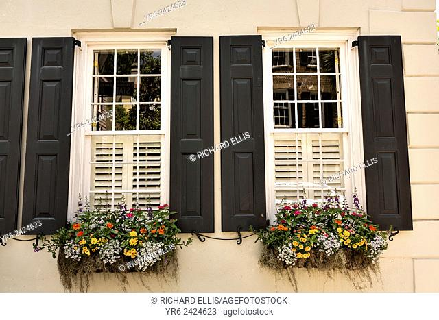 Flowers blooming in window boxes with traditional shutters in historic Charleston, SC