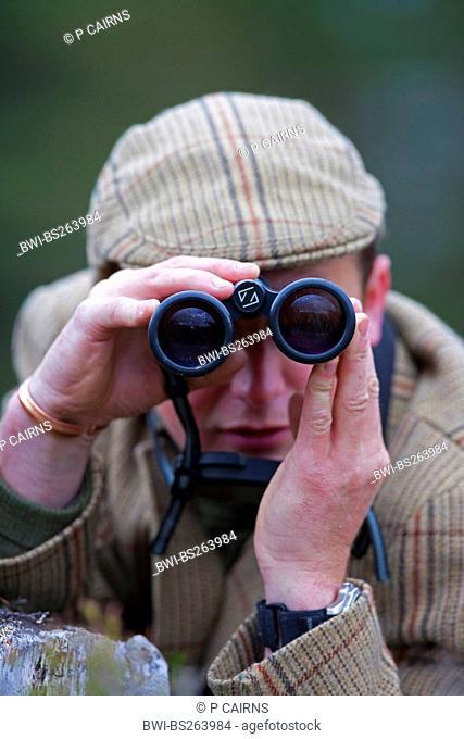 hunter looking through field glasses, United Kingdom, Scotland, Cairngorms National Park, Glenfeshie