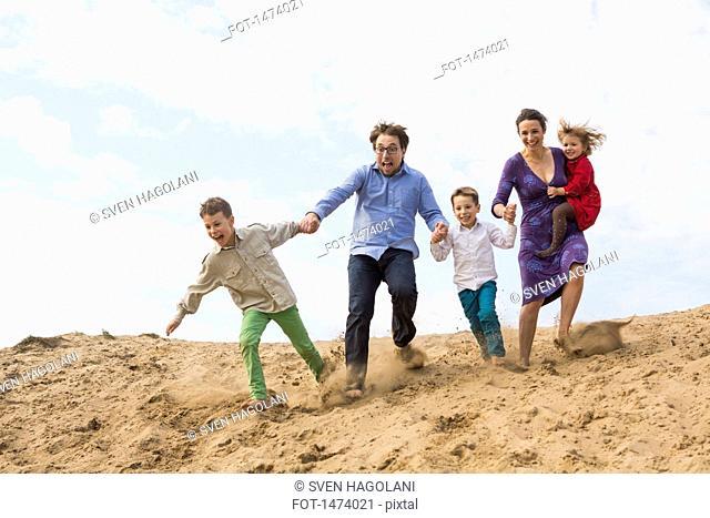 Family holding hands while enjoying on sand dune against sky