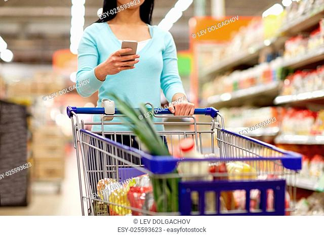 consumerism, technology and people concept - woman with smartphone and shopping cart or trolley buying food at grocery store or supermarket