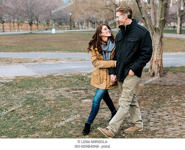 Young couple walking through park, arm in arm, smiling