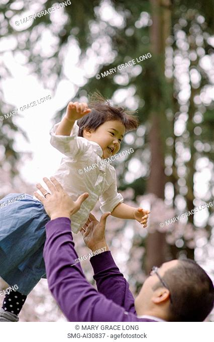 USA, Father throwing daughter (2-3) in park
