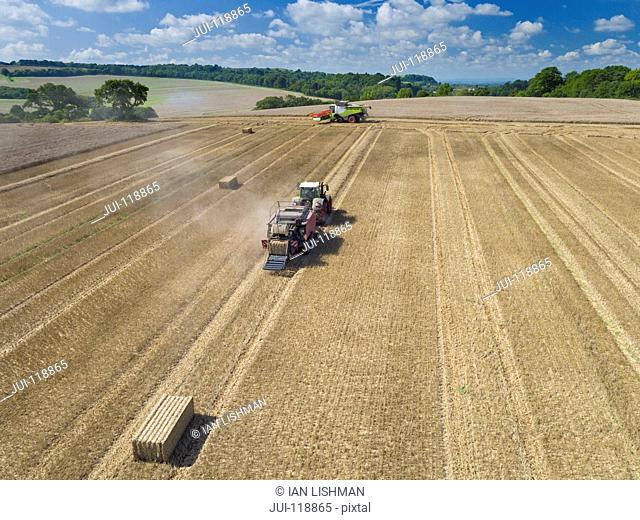Aerial view of tractor pulling baler making straw bales in harvested wheat field