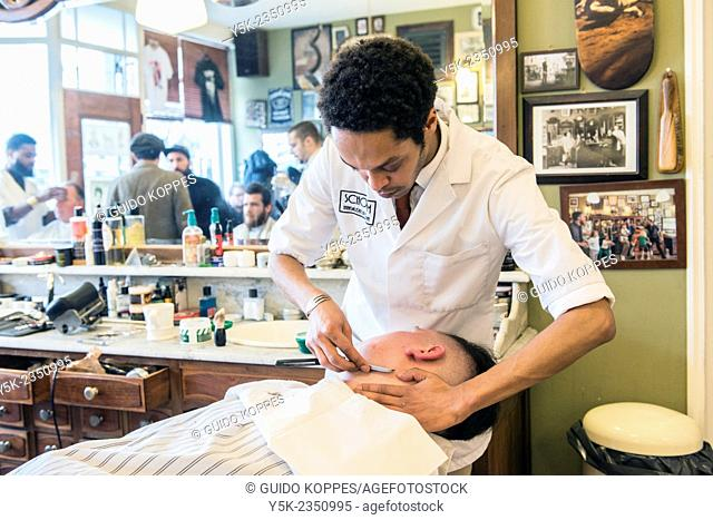 Rotterdam, Netherlands. Barber store Schorem. Male customer lying back in his barber chair while receiving a wet shave