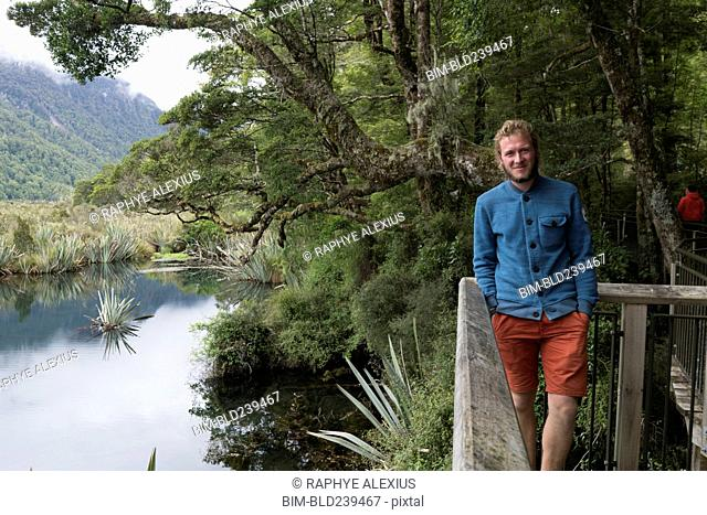 Caucasian man smiling near railing at river